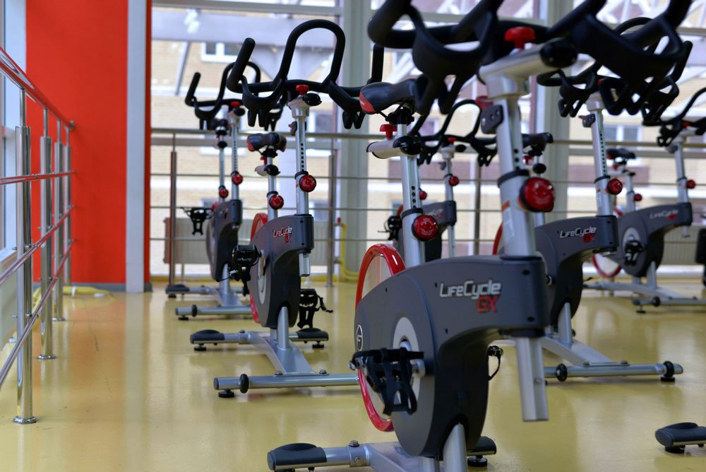 Multiple stationary bikes inside a gym studio